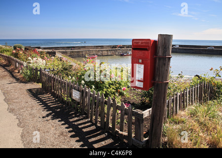 A red post box with Craster Harbour in the background. Northumberland, North EastEngland, UK - Stock Photo