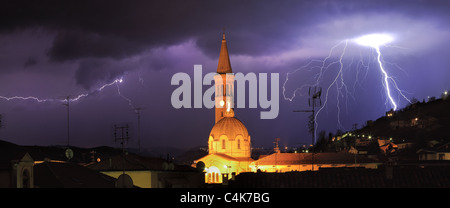 Panoramic view on lightning over Alba and surrounding hills during thunderstorm in northern Italy. - Stock Photo