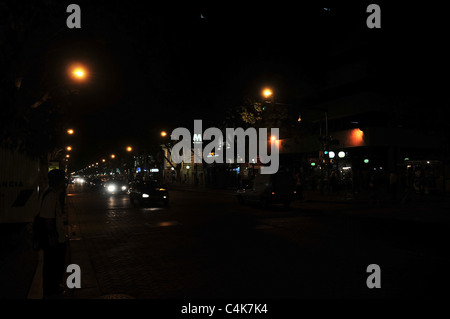 Night-time view of roadside person, yellow street light, cars, traffic, white headlights, Avenida San Martin, Mendoza, - Stock Photo