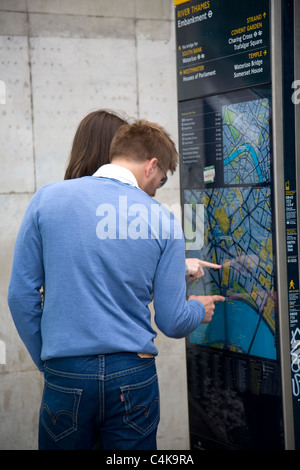 Young couple looking at Public Street Map for directions - Stock Photo