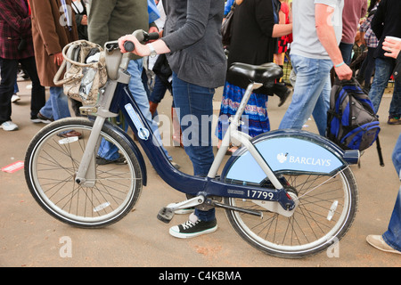 Person pushing a free to share Barclays bike on the streets of the city of London, England, UK, Britain. - Stock Photo