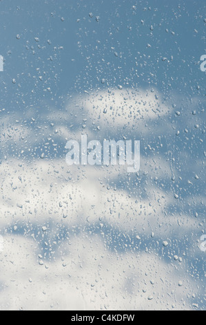 Raindrops on a window in front of a cloudy blue sky - Stock Photo