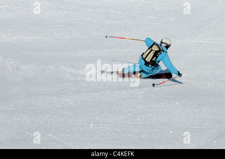 A skier carves a turn on piste in the French ski resort of Courchevel. - Stock Photo