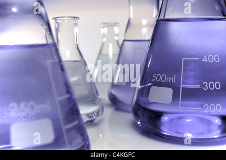 forefront of a group of purple liquid conical flasks - Stock Photo