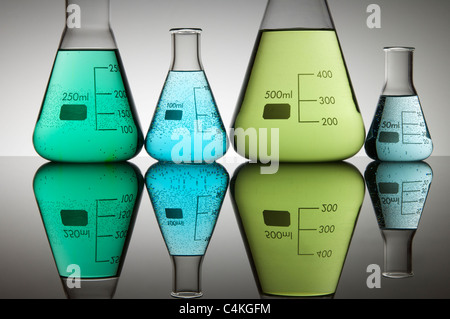 four conical flasks with green and blue liquid with a white background - Stock Photo