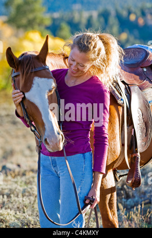 Portrait of a woman with her quarter horse in Colorado. - Stock Photo