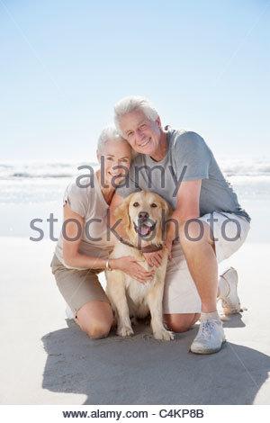Senior couple with dog on beach - Stock Photo