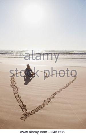 Woman sitting cross-legged in heart on beach - Stock Photo