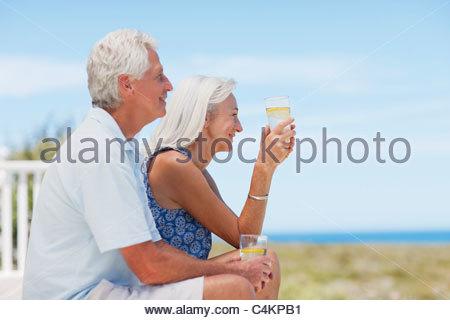 Senior couple drinking water on beach - Stock Photo