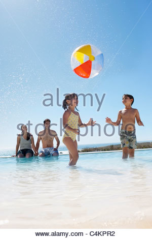Parents watching kids play with ball in swimming pool - Stock Photo