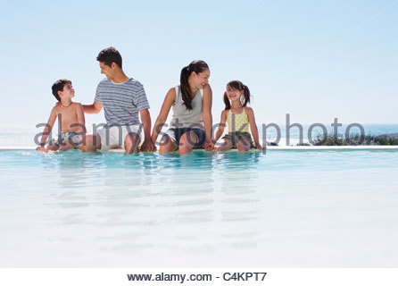Family sitting with feet in infinity pool - Stock Photo