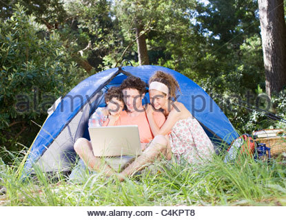 Father and kids using laptop outside tent - Stock Photo