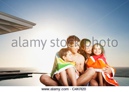 Family hugging at poolside - Stock Photo