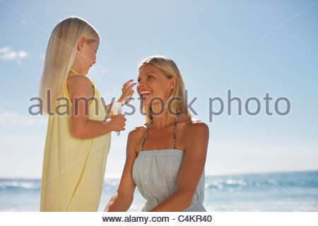 Girl applying sunscreen to mother's nose on beach - Stock Photo