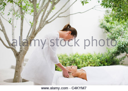 Woman receiving head massage on patio - Stock Photo