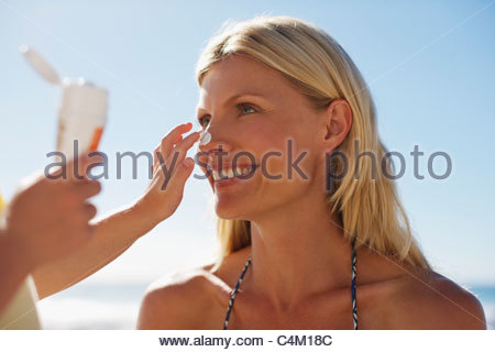 Girl applying sunscreen to mother's nose - Stock Photo