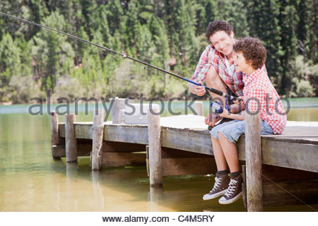 Father and son fishing off dock - Stock Photo