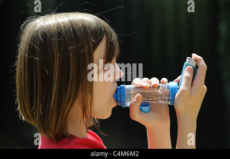 Young Asthma patient using an inhaler - Stock Photo