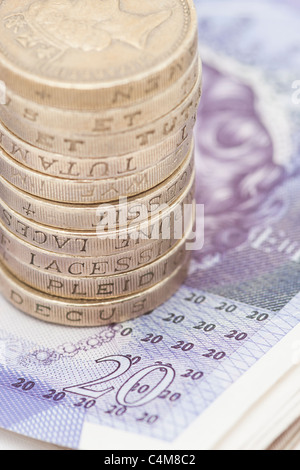 Closeup of Stack / Pile of One Pound Coins on top of Twenty Pound Notes - Stock Photo
