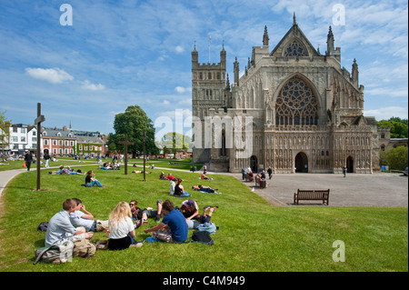 The famous West Window of Exeter Cathedral with students relaxing on the grass of Cathedral Green. - Stock Photo