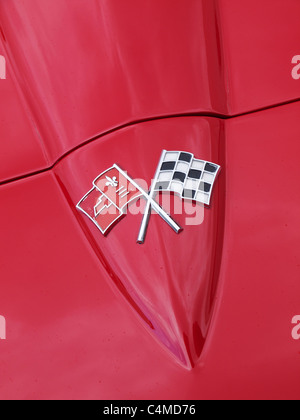 Famous Corvette bonnet badge on a late sixties red Stingray Chevrolet Corvette - Stock Photo