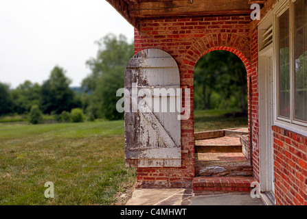 Ancient white painted door in bright red brick wall opening onto garden and trees - Stock Photo