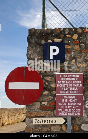 Signs for NO ENTRY TOILETTES PARKING and bilingual WARNING against thieves in Perouges Burgundy France - Stock Photo