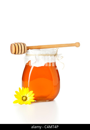 honey jar with wooden drizzler on top, flower in front, isolated on white background - Stock Photo