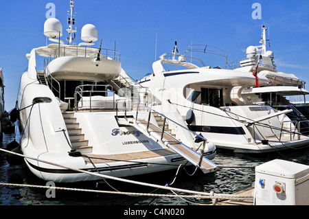 Two gleaming white luxury motoryachts moored to the quayside of the safe inner harbour of Toulon, France - Stock Photo