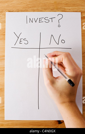 Business man making the decision of whether or not to invest - Stock Photo