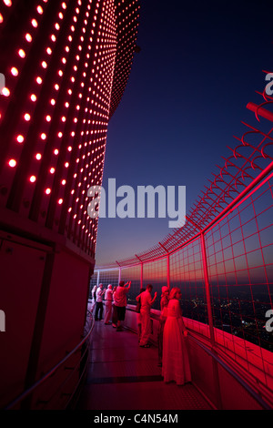 Bangkok, Thailand: tourist people looking at panoramic view from the baiyoke tower II top floor at night - Stock Photo