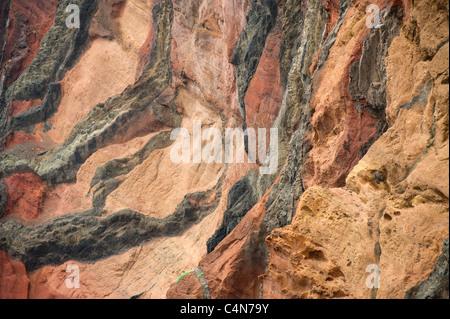 Volcanic dikes run through red ash deposits, Sao Lourenco Peninsula, Madeira - Stock Photo