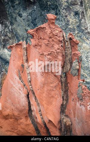Volcanic dikes run through pillar of red ash deposits, Sao Lourenco Peninsula, Madeira - Stock Photo