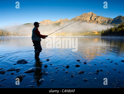 Middle age male fly fishing in Pyramid Lake, Jasper National Park, Alberta, Canada. - Stock Photo