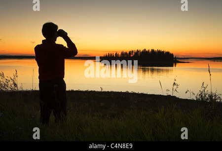 Middle age male hiker looking out over Astotin Lake with binoculars at dusk, Elk Island Park, Alberta, Canada. - Stock Photo