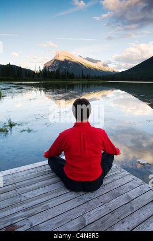 Middle age man meditating on dock at Vermillion Lake, Banff National Park, Alberta, Canada. - Stock Photo