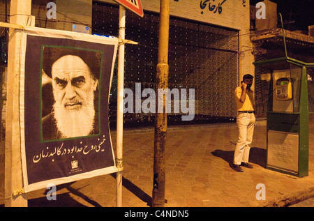 Iranian man on the phone in the street with ayatollah Khomeini poster, Yazd, Iran - Stock Photo