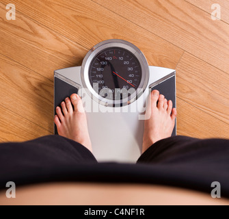 Athletic young girl measuring her weight on a scale - Stock Photo