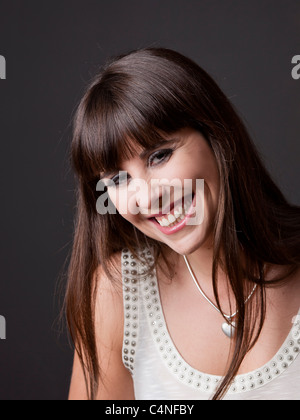 Portrait of a lovely and natural woman smiling against a grey background - Stock Photo