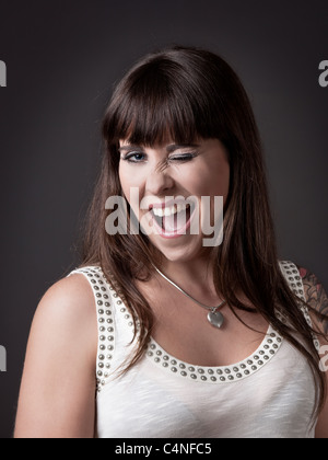 Beautiful young woman winking eyes against a grey background - Stock Photo