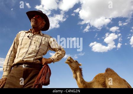 Old man at work as nomadic shepherd with dromedary in Naqsh-e Rostam, near Persepolis (Iran) - Stock Photo