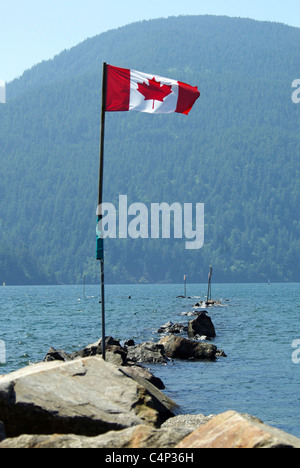 Canadian flag on flagpole taped to post on boulders in Harrison Lake,  B.C., Canada - Stock Photo