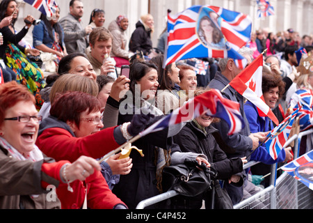 Royal Wedding 2011: Spectators wave flags on Whitehall - Stock Photo