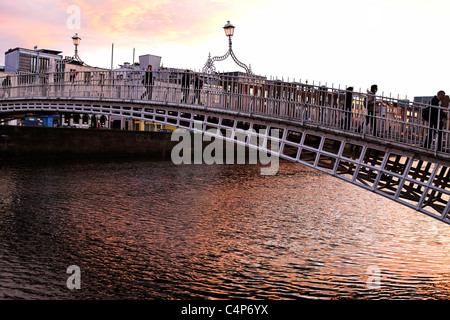 People Crossing Bridge Over the Liffey River Dublin Ireland - Stock Photo