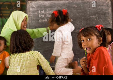 Children attend a makeshift school at a camp for people displaced by the tsunami in Banda Aceh, Indonesia - Stock Photo