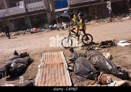 Two young boys cycle past corpses laid on the street in the wreckage caused by the tsunami and earthquake, in Banda - Stock Photo