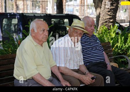 Three old Spanish men sitting on a park bench along the Paseo del Parque, Malaga, Costa del Sol, Malaga Province, - Stock Photo