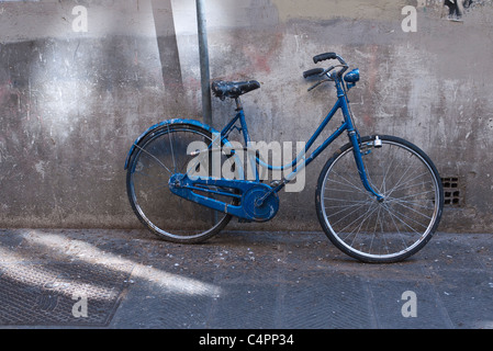 A blue woman's bicycle leans against a wall in the shade in Florence, Italy. - Stock Photo