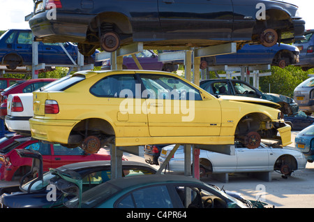 Cars stacked up in a scrapyard. - Stock Photo