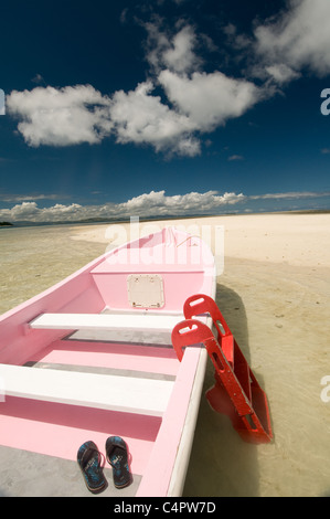 Pink boat on sandy beach of small island in the Mamanuca volcanic group of islands Fiji South Pacific - Stock Photo